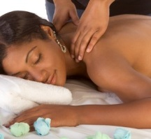 Beautiful young black female is relaxing while being massaged in spa